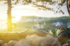 A man sleeping in sleeping bag. A man sleeps in a sleeping bag at sunrise stock photography