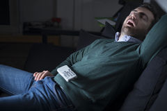 Man sleeping and snoring in front of television Royalty Free Stock Image
