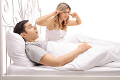 Man sleeping and snoring next to woman plugging her ears. Man sleeping and snoring next to a women plugging her ears isolated on white background Stock Photo