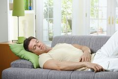 Man sleeping on sofa. Goodlooking man in causal wear sleeping on sofa with remote control in hand Royalty Free Stock Photos