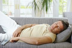 Man sleeping on sofa stock photos