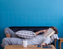 Man sleeping on sofa with book covering his face Royalty Free Stock Photography