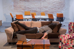 Man sleeping on a sofa  in a creative office Royalty Free Stock Image