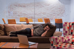 Man sleeping on a sofa  in a creative office Royalty Free Stock Photo