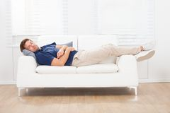 Man sleeping on sofa at home Stock Images