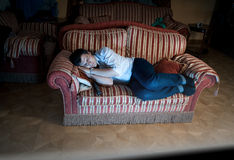 Man sleeping on sofa at night near TV Royalty Free Stock Photos