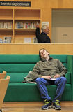 Man is sleeping on sofa in public library Royalty Free Stock Image