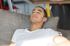 Man sleeping on sofa. Young black man in white t-shirt relaxing on grey sofa indoors lying on big cushion with his eyes closed Royalty Free Stock Photos