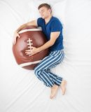 Man sleeping with soft ball toy. Top view photo of young man sleeping in an embrace with a large soft ball toy and dreaming of sport Stock Photography
