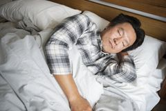 A man sleeping soundly on the bed Stock Image