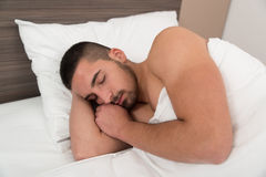 Man Sleeping Soundly In His Bed. Handsome Young Male Student Happily Sleeping In White Bed Stock Image