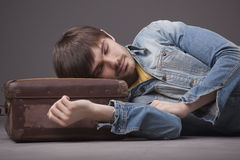 Man sleeping on suitcase Stock Photography