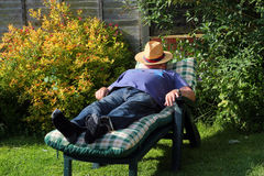 Man sleeping on a sunbed. A man lying on a sunbed in the sunshine asleep with his hat over his face Stock Photography