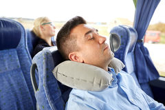 Man sleeping in travel bus with cervical pillow. Transport, tourism, rest , comfort and people concept - men sleeping in travel bus with cervical neck inflatable Stock Photography