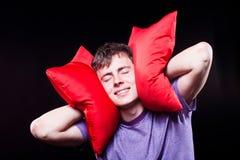 Man sleeping between two pillows Stock Photo