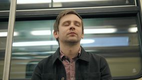 Man sleeping in a underground Metro subway train. Tired worker student sleep after work, hard day, illness, fatigue