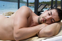 Man sleeping  on a white  sunbed  on the beach Royalty Free Stock Images