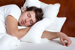 Man sleeping. Yong man sleeping in his bed on white pillow Stock Images