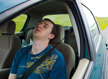 The man sleeps in the car.  Stock Image