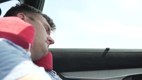 A man sleeps in the car in the back seat.  stock footage