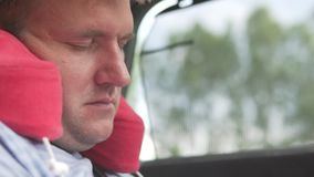 A man sleeps in the car in the back seat. Close-up of a tired traveler`s face with a traveling pillow stock video