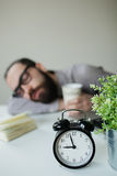 Man sleeps in office on table over laptop with coffee in hand Royalty Free Stock Photography