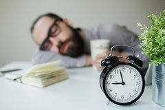 Man sleeps in office on table over laptop with coffee in hand Royalty Free Stock Photos