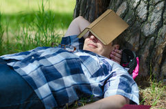 Man sleeps with open book near old pine. Man sleeps with an open book near the old pine royalty free stock images
