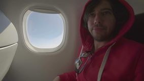 A man sleeps on a plane. he had a nightmare. wakes up scared.  stock video footage