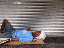 A man sleeps on a sidewalk just outside a closed store Stock Images
