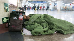 Man Sleeps in Train Station Hallway. A man lays down in the hallway of the Beijing train station during Spring Festival travel rush. He sleeps on the floor in a Stock Photography