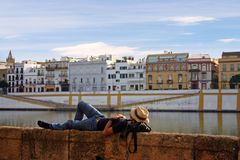 Man sleeps on wall. At river in city Royalty Free Stock Photos