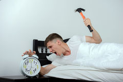 Man Sleeps. Young man tries to break the alarm clock with hammer royalty free stock image