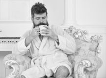 Man sleepy in bathrobe, drinks coffee, enjoying aroma in luxury hotel in morning, white background. Man with beard and. Mustache enjoys morning while sitting on royalty free stock photo