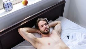 Man sleepy drowsy unshaven bearded face having rest. Pleasant relax concept. Let your body feel comfortable. Man. Unshaven handsome guy naked torso relaxing bed royalty free stock image