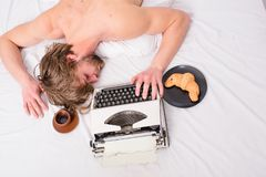 Man sleepy lay bedclothes while work. Writer used old fashioned typewriter. Author tousled hair fall asleep while write. Chapter top view. Workaholic fall royalty free stock images