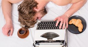 Man sleepy lay bedclothes while work. Writer used old fashioned typewriter. Workaholic fall asleep. Author tousled hair. Fall asleep while write chapter top stock image