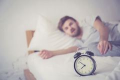 Man sleepy nationality american reaching for the alarm clock sleep. Stock Images