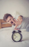 Man sleepy nationality american reaching for the alarm clock sleep. Royalty Free Stock Photo
