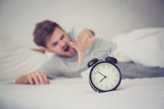 Man sleepy nationality american reaching for the alarm clock sleeping on bedroom. stock photography