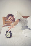 Man sleepy nationality american reaching for the alarm clock sleeping. Stock Photo