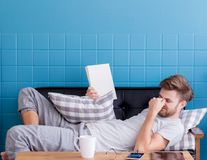 Man sleepy on old sofa with book hold hand because reading book royalty free stock images