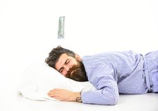 Man with sleepy smiling face lies on pillow, sleeps. Hipster with beard and mustache sleeping, dreaming of money. Man in bathrobe, businessman sleeps, white Stock Images