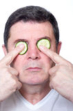 Man with slice cucumber over eyes Stock Photography