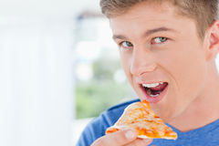 A man with a slice of pizza in his hand as he looks at the camer Royalty Free Stock Photos