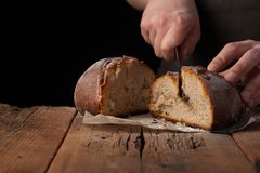 Man slices of delicious fresh bread on black background with copy space for your text. The loaf on the old rustic table.  Royalty Free Stock Images