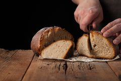 Man slices of delicious fresh bread on black background with copy space for your text. The loaf on the old rustic table.  Stock Photos
