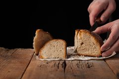 Man slices of delicious fresh bread on black background with copy space for your text. The loaf on the old rustic table.  Royalty Free Stock Photos