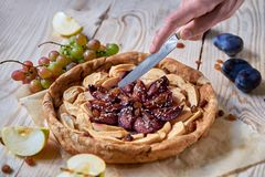 A man slices with silver knife homemade apple plums pie decorated with fresh apples, plums, grapes, brown raisins and sesame. On light wooden background. Close Stock Photos