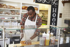 Man slicing bread behind the counter of a sandwich bar Stock Image